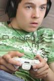 Menino que joga um jogo video Fotos de Stock