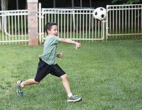 Menino que joga um menino do futebol foto de stock royalty free