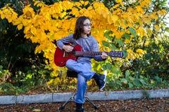 Menino que joga uma guitarra vermelha Fotografia de Stock Royalty Free