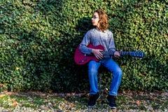 Menino que joga uma guitarra vermelha Imagem de Stock Royalty Free