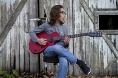 Menino que joga uma guitarra vermelha Foto de Stock