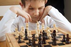 Menino que joga a xadrez imagens de stock royalty free