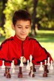 Menino que joga a xadrez foto de stock