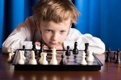 Menino que joga a xadrez Fotografia de Stock Royalty Free