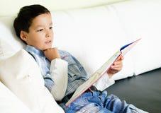 Menino que lê um livro Fotografia de Stock