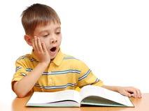 Menino que lê um livro e que boceja Fotos de Stock