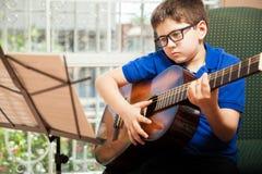 Menino que lê uma partitura da guitarra fotos de stock