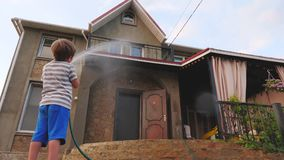 Menino que lava a casa exterior Atividade exterior do verão da mangueira da água para crianças Conceito feliz da infância Ajuda d vídeos de arquivo