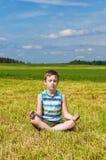 Menino que meditating no campo verde Foto de Stock