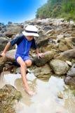 Menino que mergulha seus dedos do pé em um rockpool Fotografia de Stock