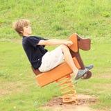 Menino que monta o cão de madeira Fotografia de Stock Royalty Free