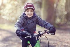 Menino que monta sua bicicleta e que ri nas folhas de outono no parque fotos de stock royalty free