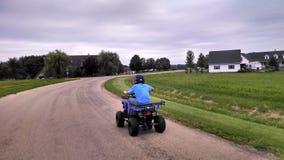 Menino que monta um ATV Imagem de Stock