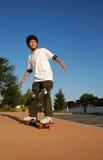 Menino que monta um skate Imagens de Stock