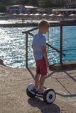 Menino que monta um skate elétrico pelo mar Equitação do homem novo no Hoverboard foto de stock royalty free