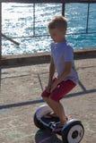 Menino que monta um skate elétrico pelo mar Equitação do homem novo no Hoverboard fotos de stock royalty free