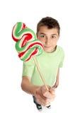 Menino que mostra doces do lollipop Imagens de Stock Royalty Free