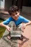 Menino que mostra fora seu recipiente pequeno dos peixes Fotos de Stock Royalty Free