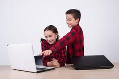 Menino que mostra um jogo de computador à menina na classe foto de stock
