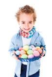 Menino que mostra uma cesta com ovos da páscoa coloridos foto de stock