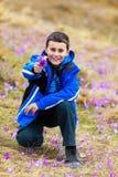 Menino que oferece um grupo de flores Fotos de Stock Royalty Free