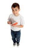 Menino que olha acima de um livro e de um sorriso Foto de Stock