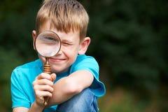 Menino que olha através da lupa com olho ampliado Fotografia de Stock Royalty Free