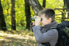Menino que olha através dos binóculos Imagem de Stock