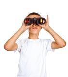 Menino que olha através dos binóculos Fotografia de Stock