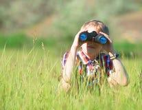Menino que olha através dos binóculos Fotos de Stock