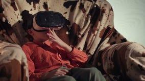 Menino que olha com os auriculares e gesticular de VR vídeos de arquivo
