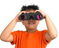 Menino que olha com um binocular Fotografia de Stock Royalty Free