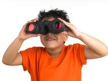 Menino que olha com um binocular Fotos de Stock