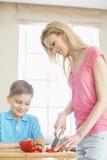 Menino que olha a mãe que corta a pimenta de sino vermelha na cozinha Imagem de Stock Royalty Free