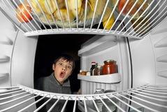 Menino que olha no refrigerador Fotos de Stock Royalty Free