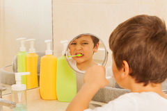 Menino que olha no vidro durante a escovadela de dente imagens de stock