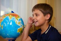 Menino que olha o globo Imagens de Stock