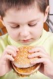 Menino que olha o Hamburger Fotografia de Stock Royalty Free