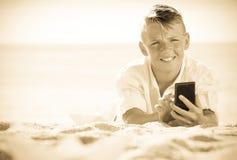 Menino que olha o telefone ao descansar na praia fotos de stock royalty free