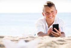 Menino que olha o telefone ao descansar na praia Imagens de Stock Royalty Free