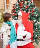 Menino que olha Santa Claus In Front Of Christmas Fotografia de Stock
