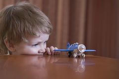 Menino que olha Toy Airplane Imagens de Stock Royalty Free