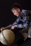 Menino que olha um globo Fotos de Stock Royalty Free