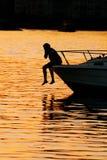Menino que oscila seus pés sobre o prow do barco Fotos de Stock Royalty Free