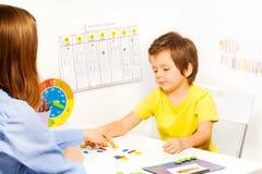 Menino que põe moedas dadas forma coloridas em ordem Fotografia de Stock Royalty Free