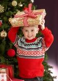 Menino que prende atual na frente da árvore de Natal Fotos de Stock