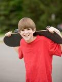 Menino que prende seu skate imagens de stock royalty free