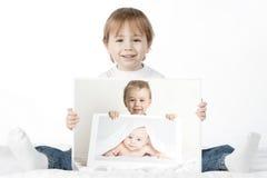 Menino que prende suas fotos do bebê Foto de Stock Royalty Free