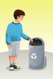 Menino que recicla o lixo no balde do lixo Fotos de Stock Royalty Free