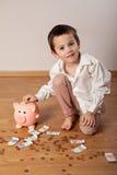 Menino que recolhe o dinheiro em um mealheiro Imagem de Stock Royalty Free